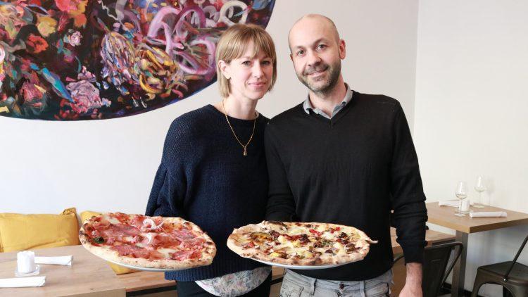 Die Inhaber der neuen Pizzeria mit großen Pizzen in der Hand.