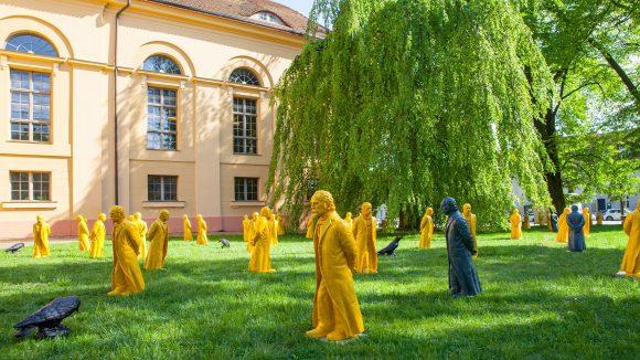 Viele gelbe und schwarze Theodor Fontane-Figuren auf einer Wiese vor der Kulturkirche Neuruppin