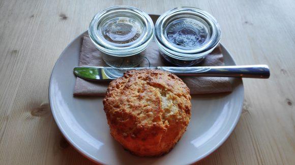 Scones auf einem Teller mit Messer und zwei kleinen Weckgläsern auf Holztisch