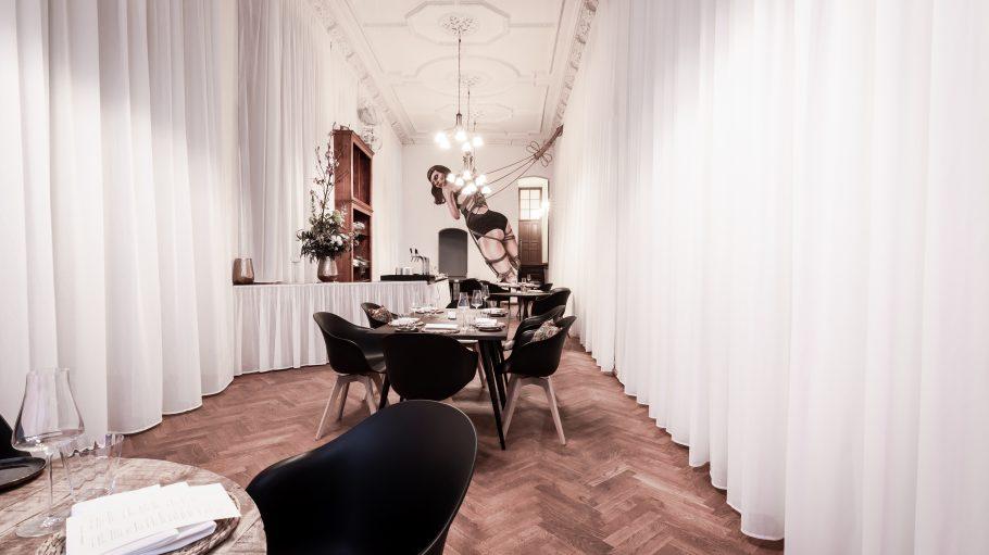 Gastraum in The Noname mit weißer Gardine und Mural