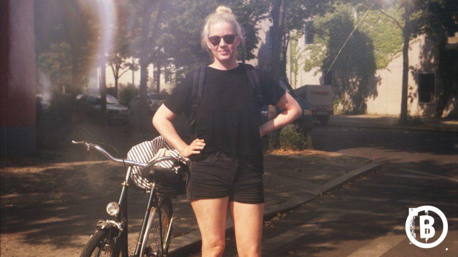Frau in Schwarz steht neben ihrem Fahrrad draußen auf der Straße