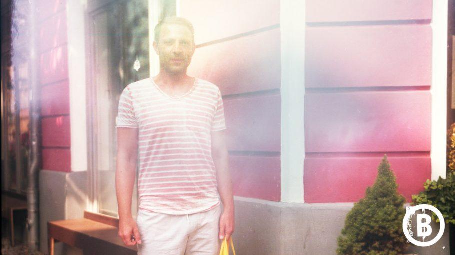 Mann in rosa weiß geringeltem T-Shirt vor rotem Haus