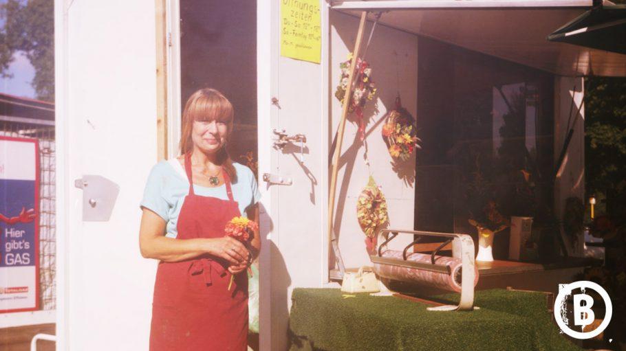 Frau mit roter Schürze und Blumenstrauß in der Hand vor Blumenladen