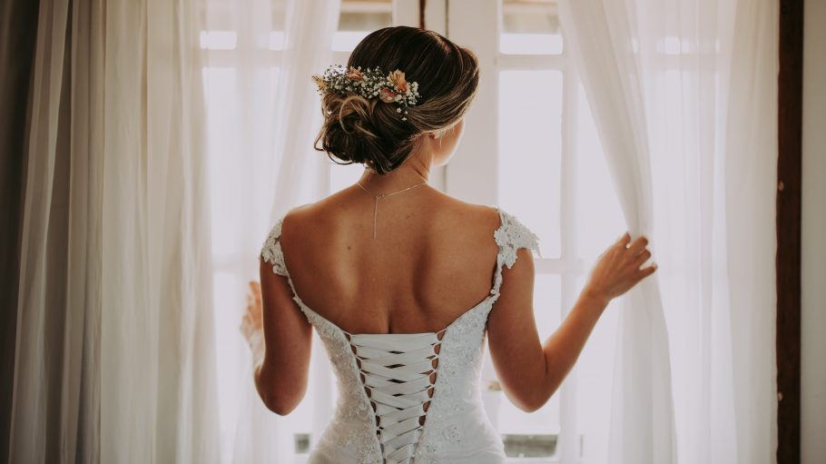 Eine Braut steht mit dem Rücken zum Beobachter am Fenster und sieht hinaus.