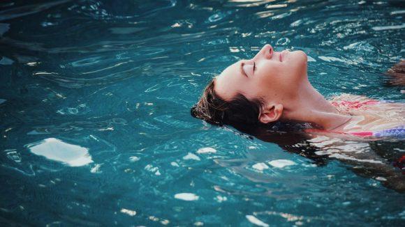 Frau schwebt im Wasser