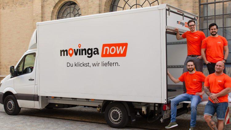 Weißer Umzugstransporter von Movinga Now mit aufgeklappter Ladefläche, auf der 4 männliche Mitarbeiter stehen und sitzen.