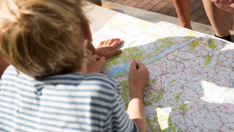 Kind liegt vor einer Landkarte und plant Fahrradstrecken.