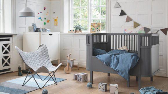 Ein Kinderzimmer mit grauem Babybett und bequemen STuhl