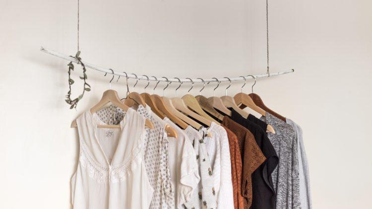 Kleiderstange mit aufgereihten Klamotten.