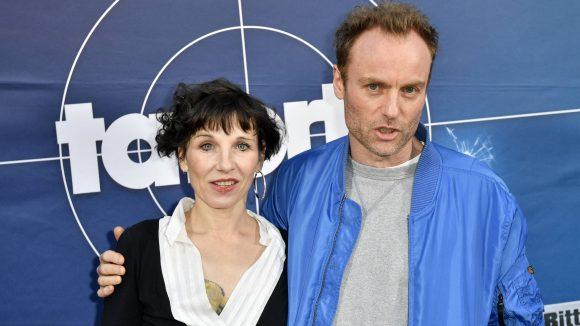 Schauspielerin Meret Becker, dunkle Haare, schwarz-weißes Kleid, und Marc Waschke, dunkelblonde Haare, blaue Jacke, stehen vor Tatort-Schriftzug