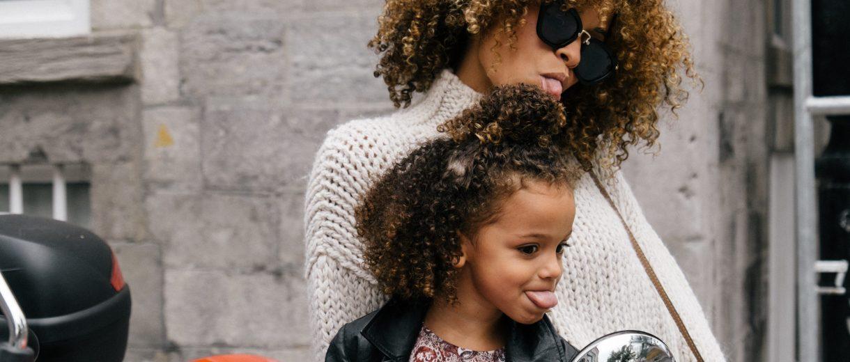 Eine Mutter streckt mit ihrer Tochter zusammen die Zunge heraus.
