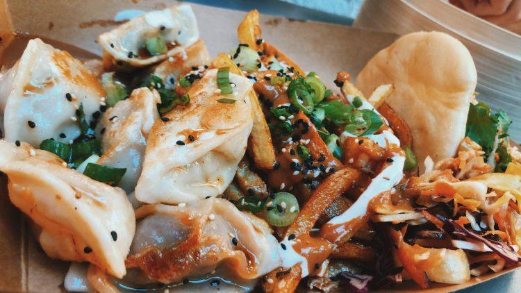 Ein Pappteller mit Bao Burger und Dumplings, daneben Pommes, stehen auf einer blauen Holzbank.