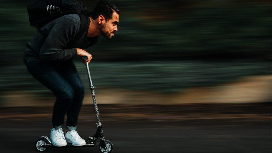 Junger Mann rast auf E-Scooter