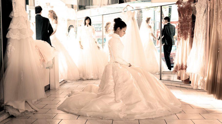 Eine Frau allein in einem Brautkleid im Brautmodengeschäft.