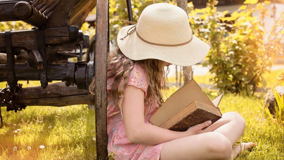 Mädchen mit Strohhut liest ein Buch auf der Wiese.