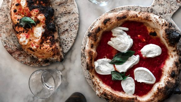 Neapolitanische Pizza mit saftigem Teig und Büffelmozarella und eine Calzone auf einem weißen Marmortisch.
