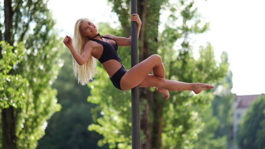 Frau in schwarzem Bikini turnt an der Stange.