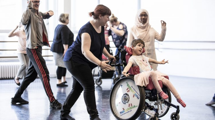 Ein Mädchen im Rollstuhl und andere Kinder mit Cerebralparese tanzen