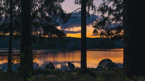 Zelt in der Dämmerung am Seeufer, drei Leute daneben, im Vordergrund Wald, am anderen Seeufer ebenfalls