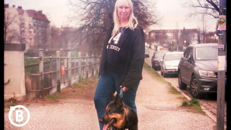 Eine Frau mit einem Schäferhund an der Leine in Neukölln.