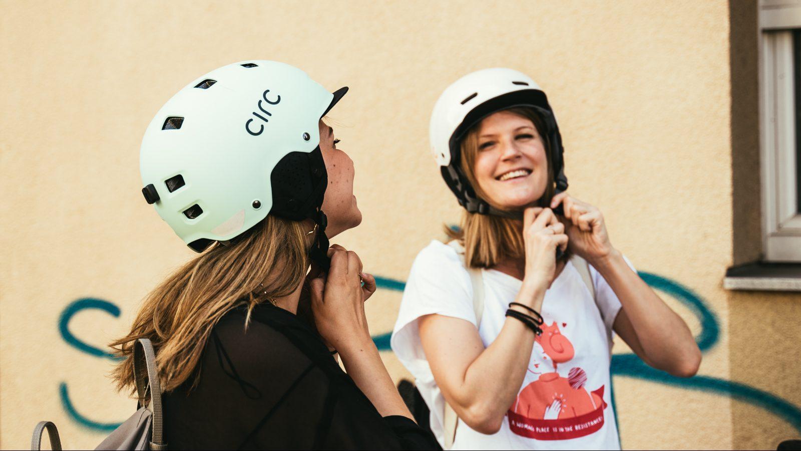 Zwei Frauen die sich Fahrradhelme zumachen