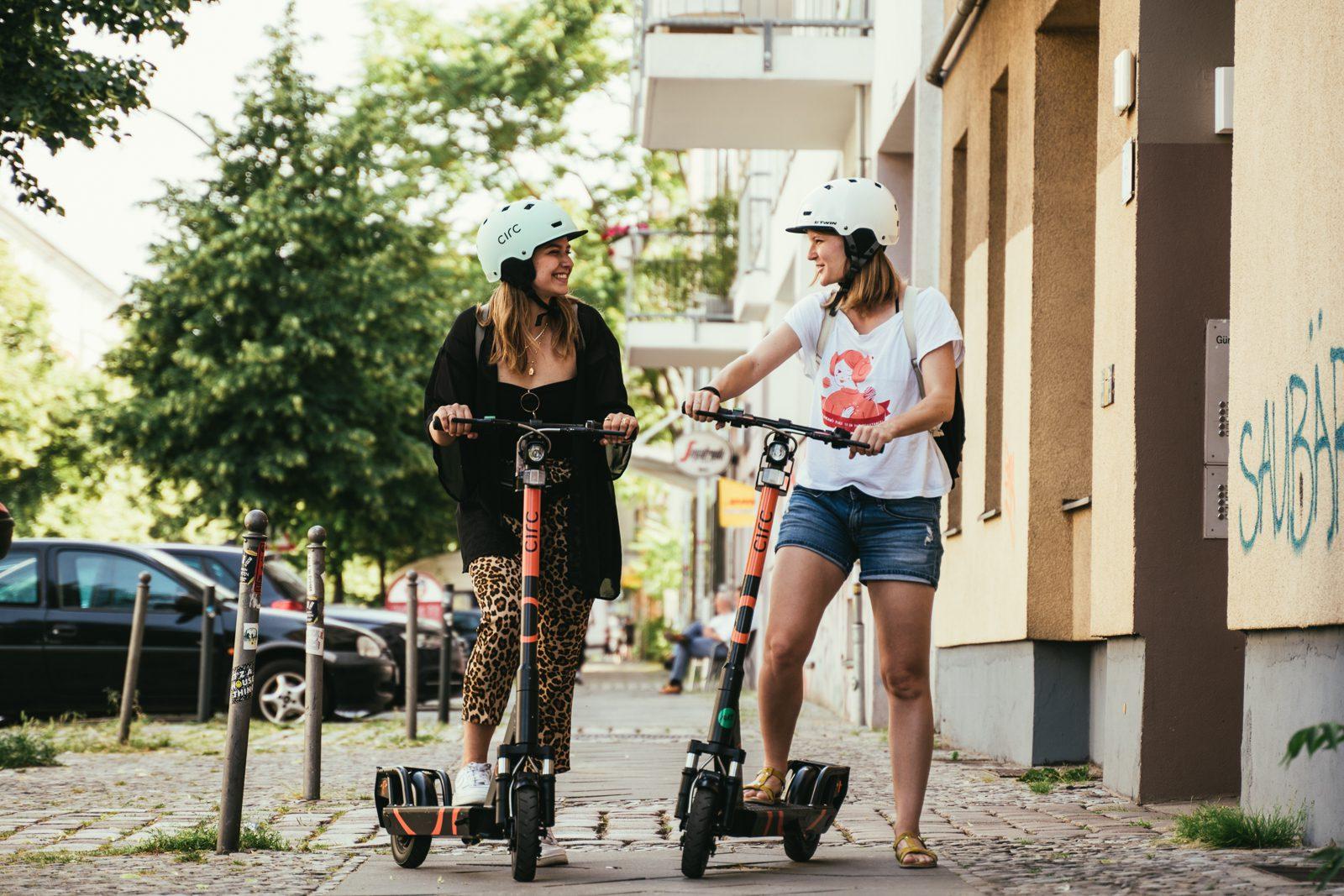 Zwei Frauen steigen auf einen E-Scooter.