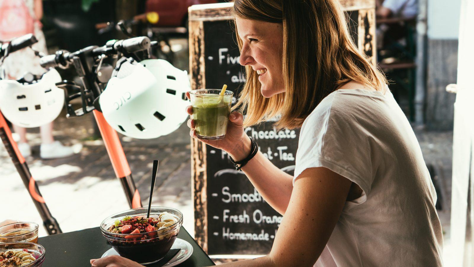 Frau trinkt hält Matcha Latte in der Hand und lacht