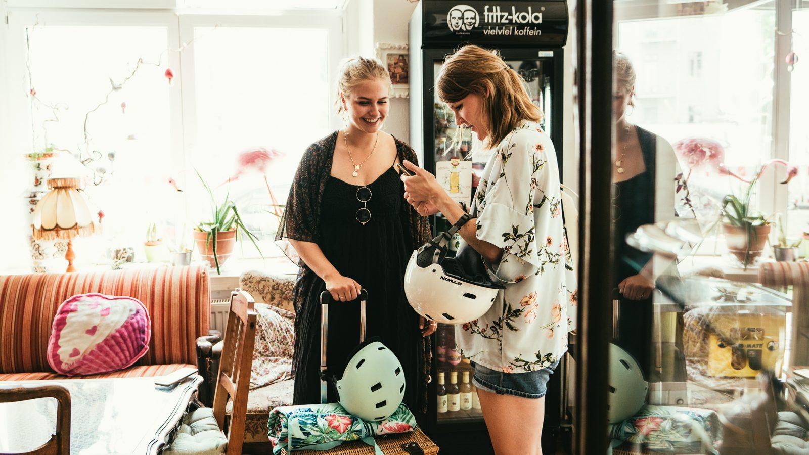 ZWei Frauen in einem cafe die auf ein Handy gucken
