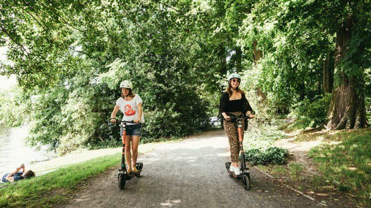 Zwei Frauen fahren auf einem E-Scooter am See entlang.