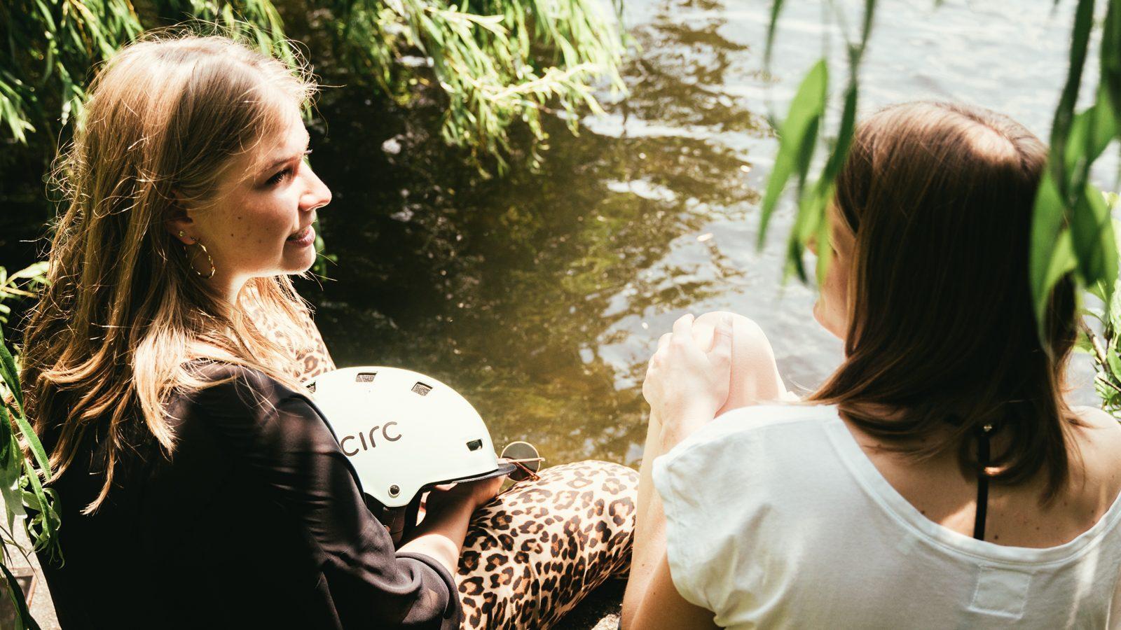 Zwei Frauen sitzen am Wasser