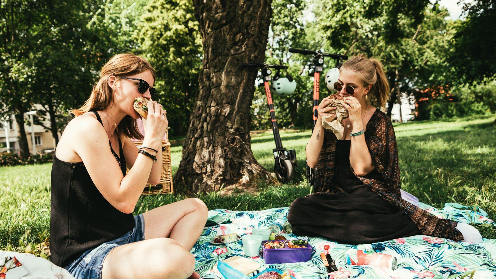 Zwei Frauen auf einer Picknickdecke im Park die ineinen Bagel beißen