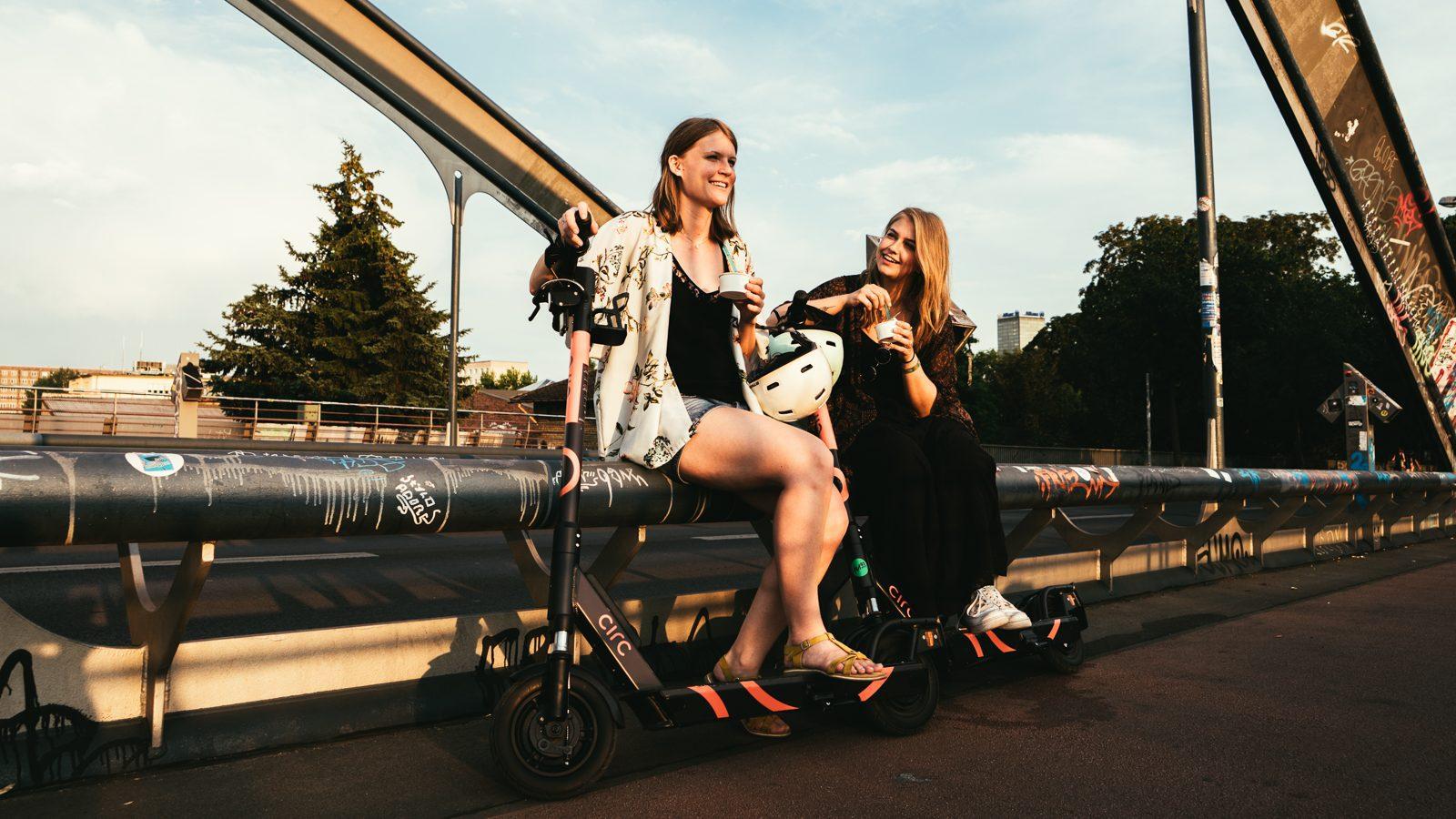 Zwei Frauen sitzen auf einer Brücke und essen Eis