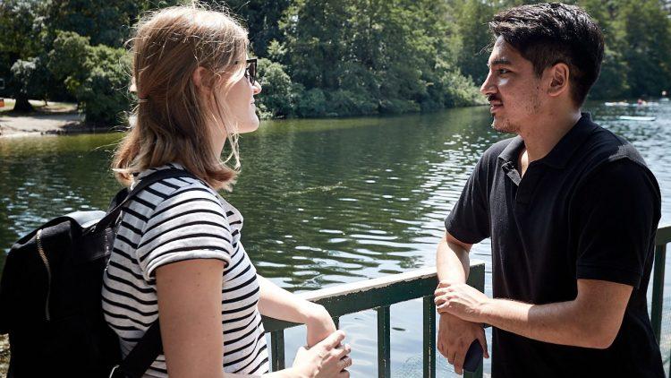 Die zwei Kollegen reden miteinander vor dem See.