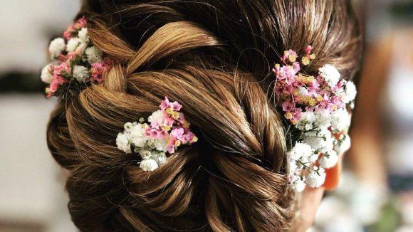 Hochsteckfrisur einer Braut mit braunen Haaren und Blumen im Haar.