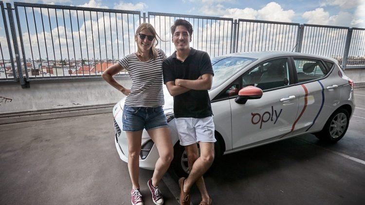Zwei Menschen stehen auf einer Tiefgarage vor dem Oply-Auto