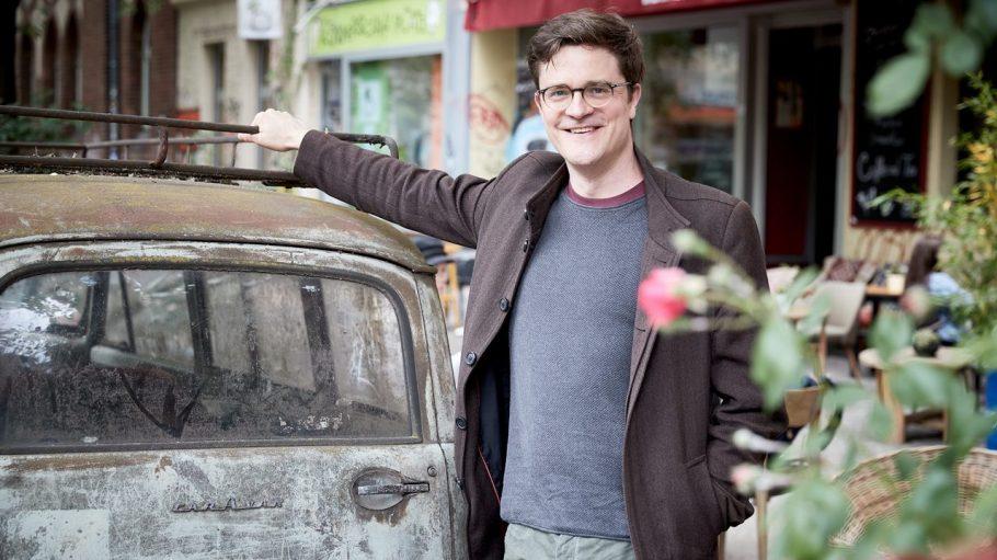Bodo Wartke lehnt sich an ein verostetes Auto vor dem Café Zazza. Im Vordergrund ein Auto.