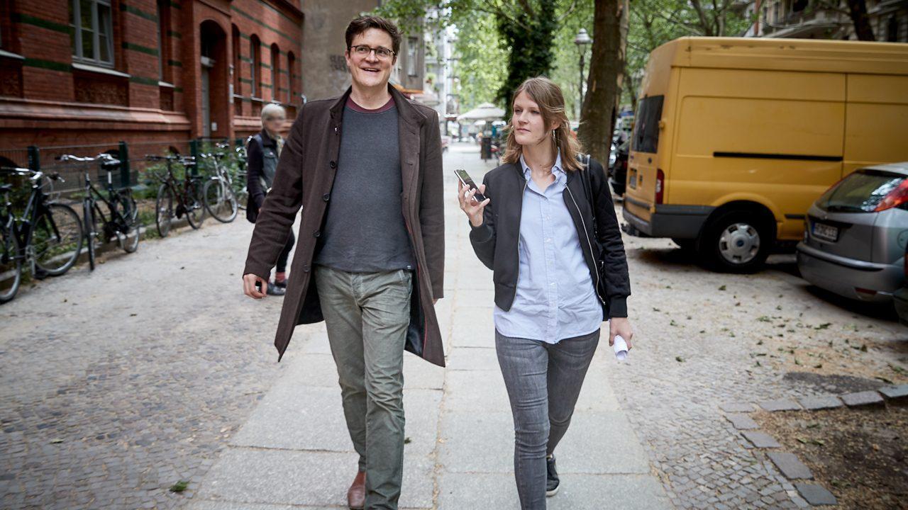 Die Reporterin und Bodo Wartke gehen nebeneinander auf der Straße.