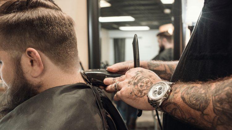 Friseur rasiert einem Mannmit bart und dunklen Haaren den Nacken aus.