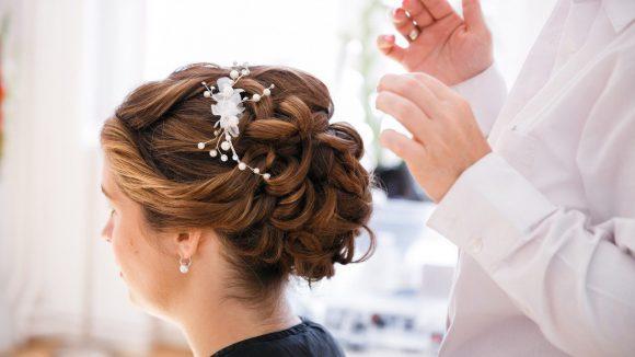 Braut mit braunen Haaren und lockiger Hochsteckfrisur und Accessoire im Haar.