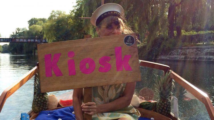 Eine Frau sitzt auf einem Boot mit Kapitänsmütze auf dem Kopf und einem Schild mit der Aufschrift Kiosk in der Hand.