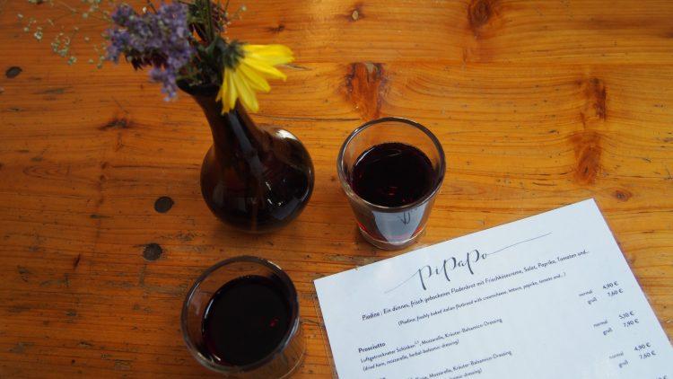 Die Speisekarte des Pipapo auf der Bierbank, daneben zwei Lambrusco und Blumen.