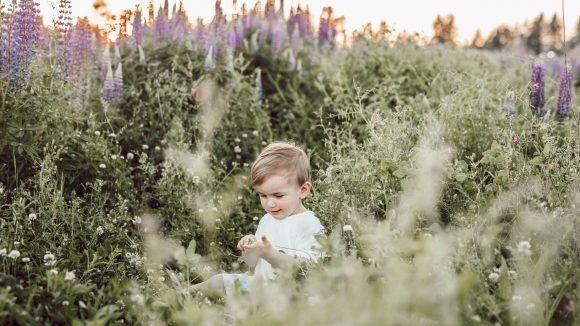 Ein Kind steht draußen in hochwucherndem Garten.