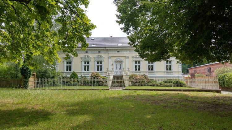 Denkmalgeschütztes einstöckiges gelbes Haus mit weißen Fensterrahmen und Stuck, mit Garten und davor grüner Wiese in Alt-Lübars