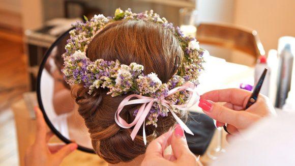 Brautfrisur mit Blumenkranz in rosa und lila und lässigem Knoten im Nacken.