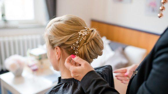Braut mit blondem Haar und lässigem Dutt und Accessoire im Haar
