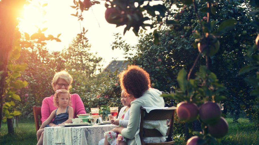 Eltern sitzen mit ihren Kindern draußen am Tisch beim Essen.