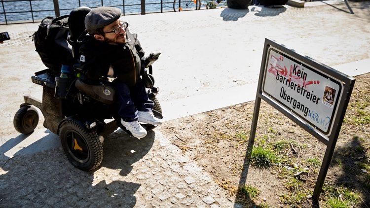 """Raúl Krauthausen vor einem Schild, auf dem """"Kein barrierefreier Übergang"""" steht."""