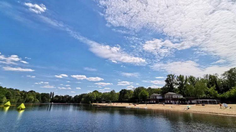 Blick auf den Plötzensee, rechts der Strand und Gebäude des Strandbads, um den See Bäume, blauer Himmel mit Wolken