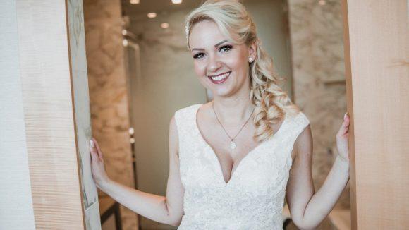 Braut mit blonden Haaren und halbhochgesteckter Frisur und weißem Brautkleid lächelt in die Kamera.