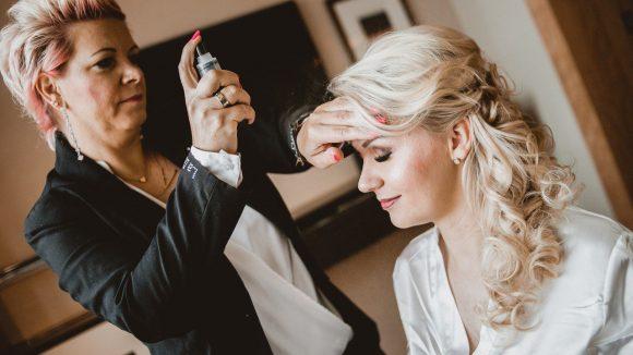 Blonde Braut mit halber Hochsteckfrisur wird von Andrea Jacobeit von La Dolce Vita zurecht gemacht.